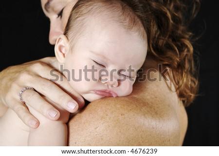Baby asleep on mommas shoulder - stock photo