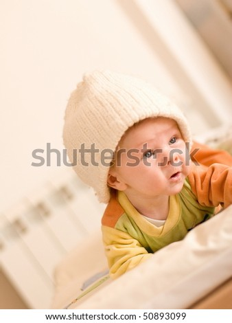 baby at six months crawling covered with hat - stock photo