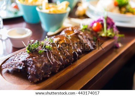 Baby back ribs with sauce served on a wooden plate with side dishes and sauces - stock photo