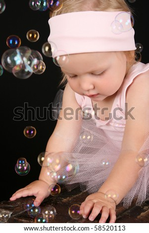 Baby ballerina playing amongst lots of bubbles - stock photo