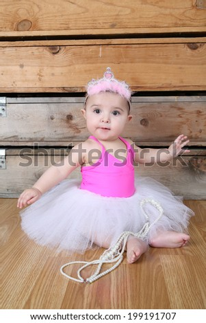 Baby ballerina wearing a white tutu and pink bodysuit  - stock photo