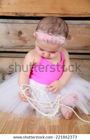 Baby ballerina wearing a white tutu and pink bodysuit  - stock photo