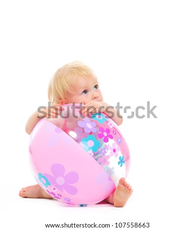 Baby behind beach ball looking on copy space - stock photo