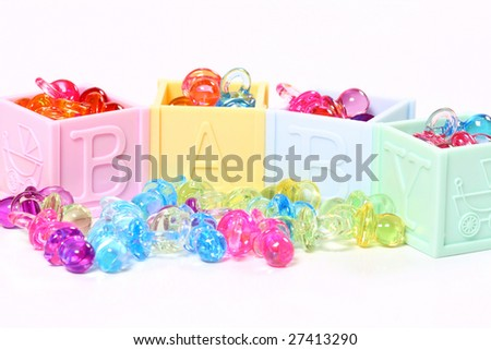 baby blocks filled to over flowing with little plastic pacifier baubles - stock photo