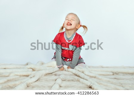 Baby blonde girl is sitting and licking on a white background - stock photo