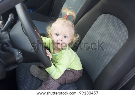 Baby blonde girl staring from the driving wheel in a car. - stock photo