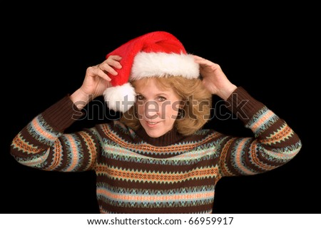 Baby boomer woman putting on a Santa hat over a black background - stock photo