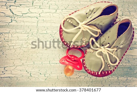 baby booties and nipple pacifier on a wooden table, retro vintage style - stock photo