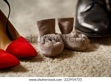 Baby booties between parent's shoes - stock photo