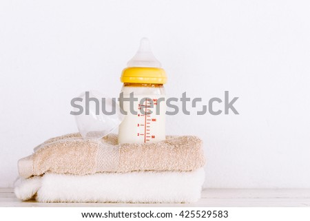 Baby bottle with milk on towel on wooden table - stock photo