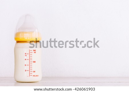 Baby bottle with milk  on wooden table - stock photo