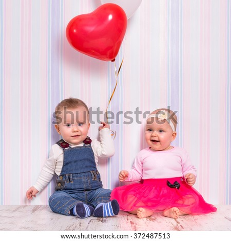 Baby boy and girl playing with heart balloons for valentines day - stock photo
