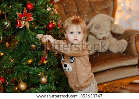 Baby boy blonde in beige sweater dresses up Christmas tree, hang the ball at him and looking at the camera - stock photo
