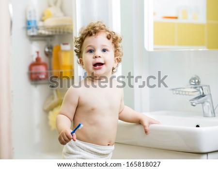 baby boy brushing teeth in bathroom - stock photo