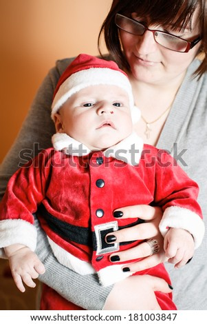 Baby boy dressed in a Santa Claus costume being held by his mother - stock photo
