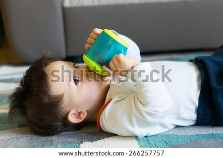 Baby boy drinking from a plastic bottle lying on the floor - stock photo