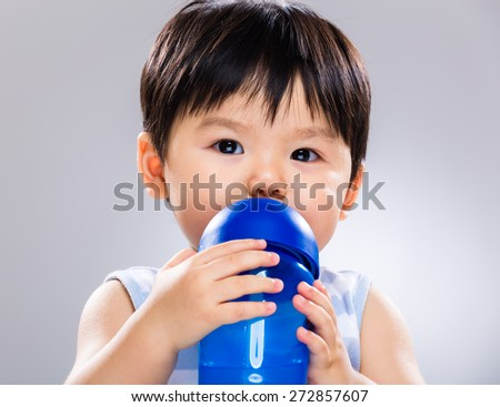 Baby boy drinking water using plastic bottle - stock photo