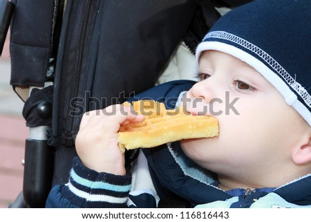 Baby boy eat waffle - stock photo