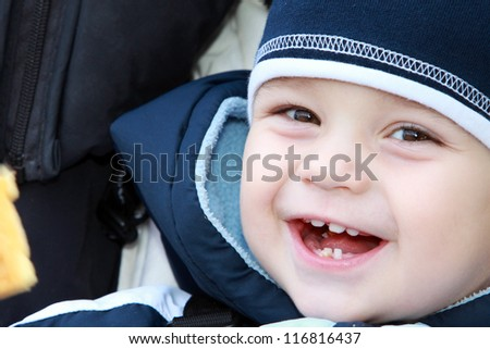 Baby boy eat waffle and laughs - stock photo
