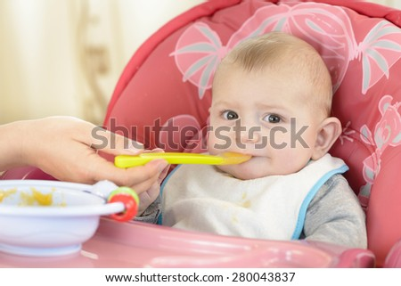 Baby boy eating in a high chair at home - stock photo