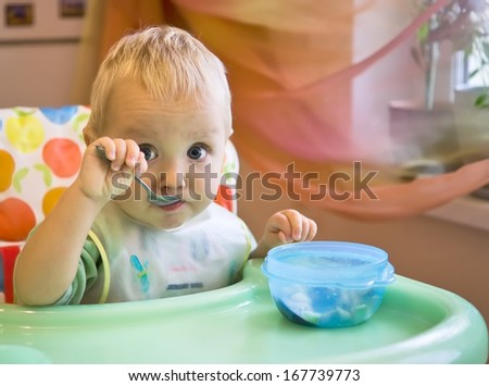 Baby boy eats with spoon himself - stock photo