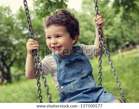 Baby boy having fun on a swing. - stock photo