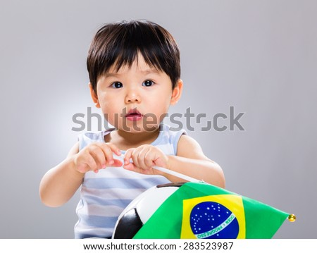 Baby boy hold with soccer ball and Brazil flag - stock photo