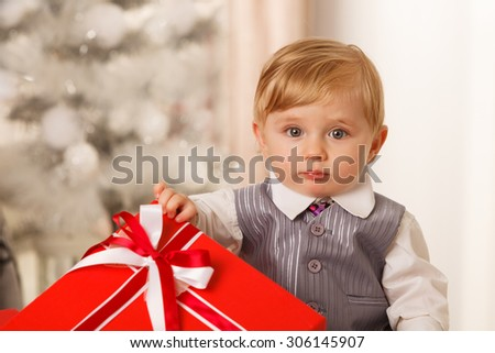 Baby boy holds a big red gift box - stock photo