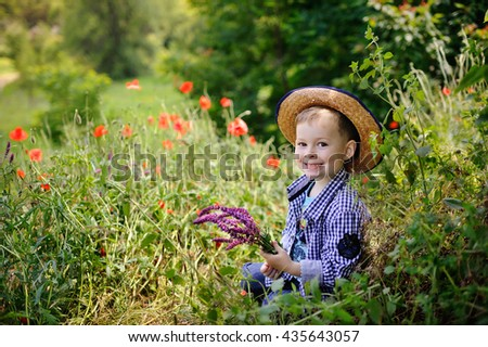 baby boy in a plaid shirt and hat on a background of poppy field. Baby boy with a bouquet of wildflowers. Portrait of a child on a background of poppy field - stock photo