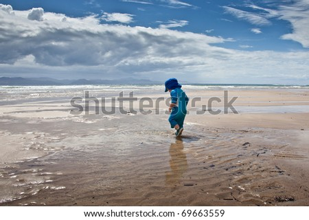 Baby boy in blue sunsuit walking on large beach - stock photo
