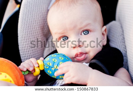 baby boy in car seat holding a toy in his hand - stock photo