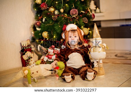 Baby boy in carnival costume near Christmas tree - stock photo
