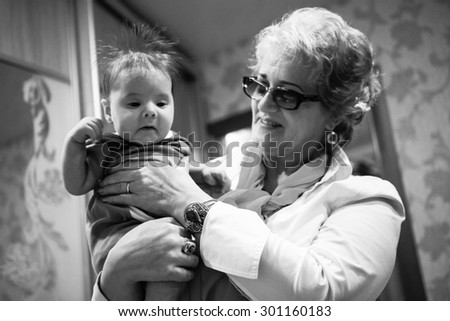 Baby boy in grandma's hands. Woman holding the baby and smiles. Black And white colors - stock photo