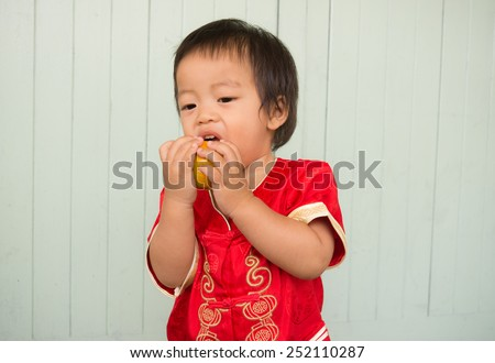 baby boy intend and tries  to eat  orange happy chinese little boy new year in Chinese style dress - stock photo
