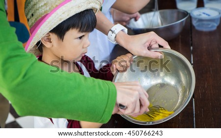 Baby boy is a cooking class. Children are taking Bakery lesson. Mother helping her child preparing pastry. - stock photo