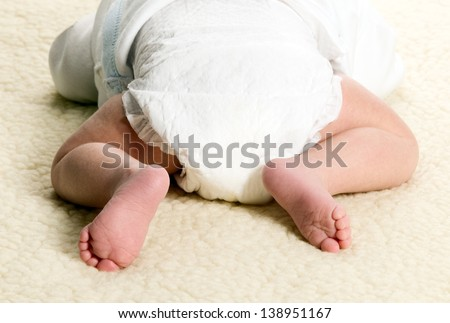 Baby boy is lying with diapers on furry blanket - stock photo