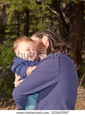 Baby boy laughing when his dad cuddles him - stock photo