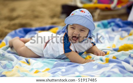 Baby boy laughing while laying on a colorful beach towel. - stock photo