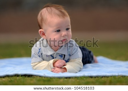 Baby Boy Laying on Front Outside on Blanket. Infant boy laying on a blanket outside while looking to the side. Shallow DOF. - stock photo