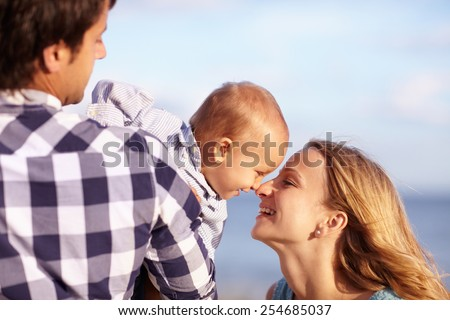 Baby boy leaning over his dad's shoulder to playfully touch noses with his beautiful smiling mother - stock photo