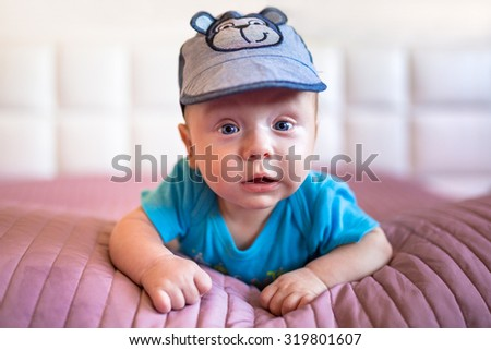 Baby boy lying in bed - stock photo