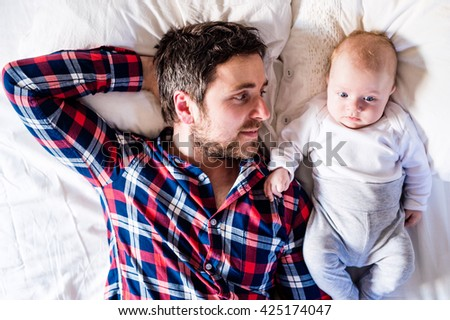 Baby boy lying on bed, next to his father - stock photo