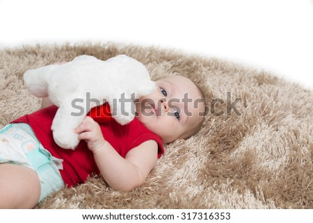 baby boy lying on his back on a brown carpet, holding a white bear toy - stock photo