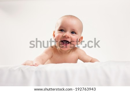 Baby boy on his tummy, smiling on the white background.  - stock photo
