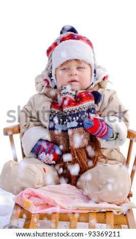 Baby boy on wooden sledge in winter - stock photo