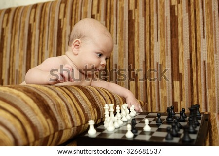 Baby boy playing chess on the sofa at home - stock photo