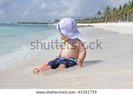 Baby boy playing in ocean waves on the beach - stock photo