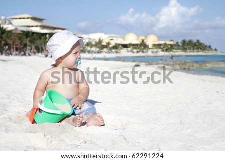 Baby boy playing in sand on a tropical beach - stock photo