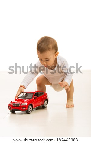 Baby boy playing with car toy home  and standing on the floor - stock photo