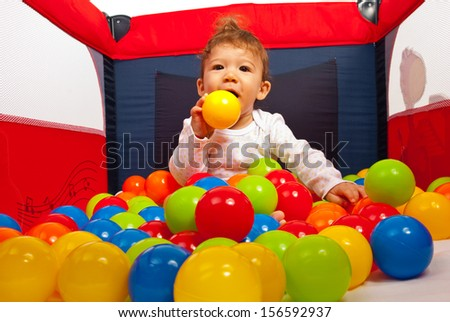 Baby boy playing with colorful balls in playpen  - stock photo